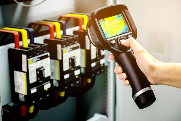 Análise termográfica e sua importância: profissional analisando um quadro elétrico.