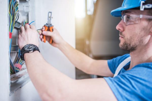 Dicas de instalação elétrica para um novo projeto: profissional instalando fiação elétrica.